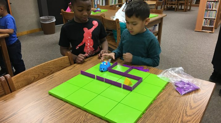 Kindergarten students coding Colby the mouse to go through a maze.