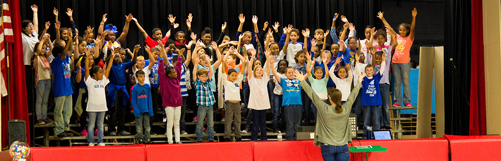 Students with Arms Up Singing