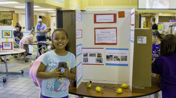 Girl Standing next to Science Experiment
